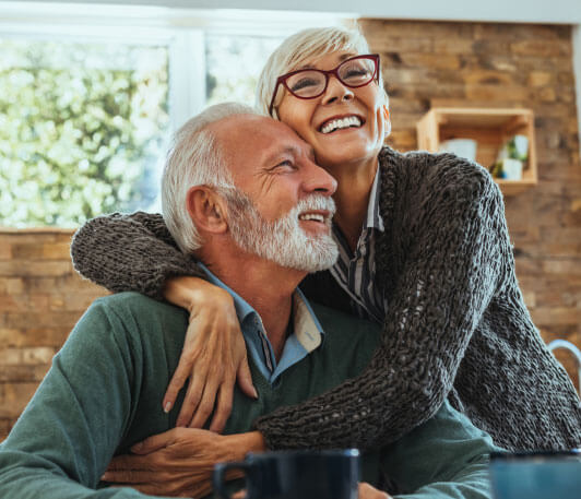An elderly man and woman embracing each other, smiling and looking in different directions